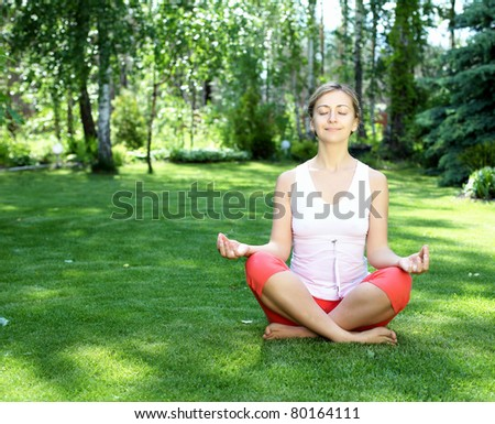 Young girl in a white shirt and red pants doing yoga outdoors - stock photo