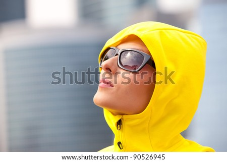 young girl in a yellow hood with black sunglasses - stock photo