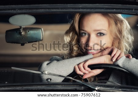 young girl in an old car - stock photo
