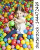 Young girl in ball pit throwing colored balls - stock photo
