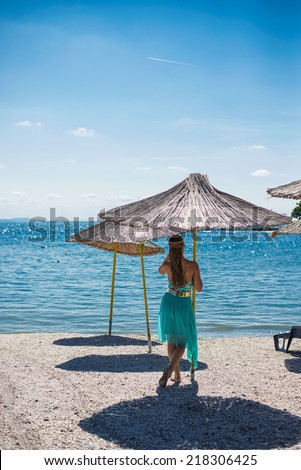 young girl in beach, in the shadow of umbrella, sunbathing - stock photo