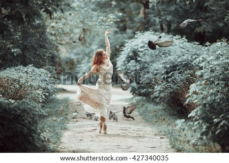 Young girl in beautiful dress and pointe shoes dancing on the street with flying pigeons.