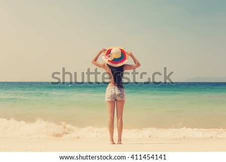 Young girl in big hat standing on ocean beach. Summer, sun, vacation and travel - stock photo