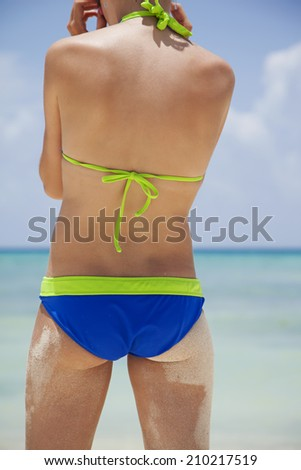 Young girl in bikini on the beach background