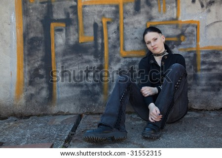Young girl in black sitting in front of graffiti wall - stock photo