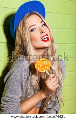 young girl in blue baseball cap against green brick wall holds round orange lolipop - stock photo
