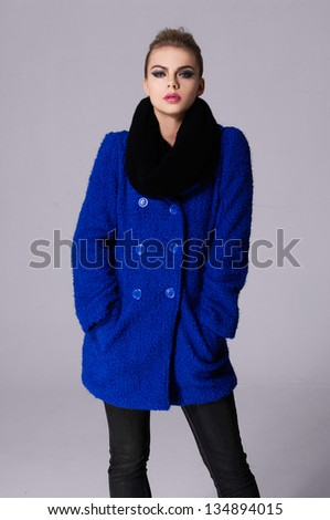 young girl in blue coat standing on gray background - stock photo