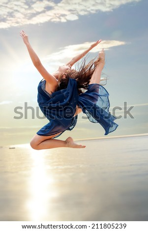 Young girl in blue dress doing Elegant rhythmic jump at sunset. - stock photo