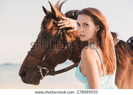Young girl in blue dress posing with a horse  - stock photo