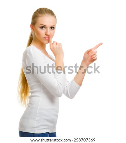 Young girl in blue jeans shows pointing gesture isolated - stock photo