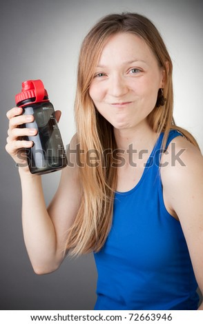 young girl in blue shirt with a water bottle in her hands - stock photo