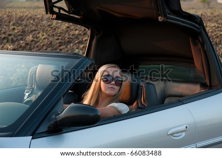 young girl in cabrio car, on sunset light - stock photo