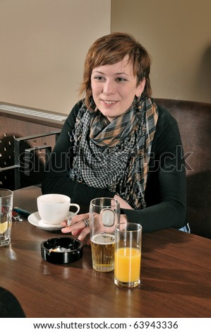 Young girl in cafe smiling and smoking - stock photo