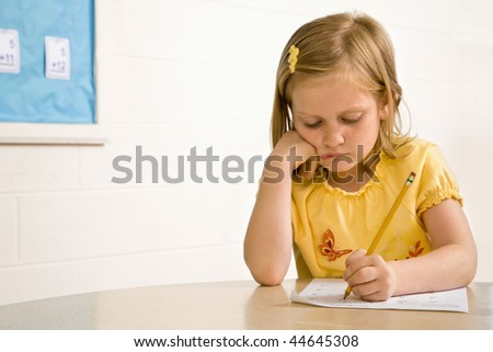 Young girl in classroom writing on paper. Horizontally framed shot. - stock photo
