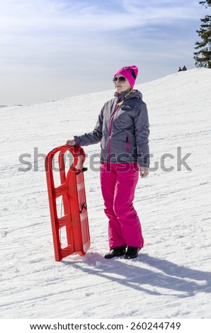 Young girl in clothes for skiers, pleasure, posing with red sled. - stock photo