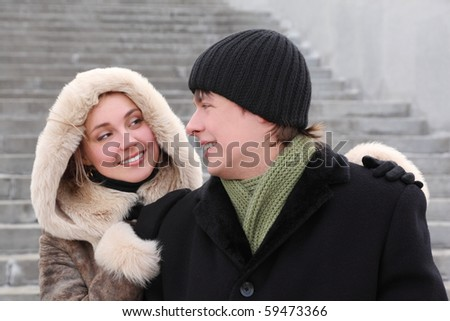 young girl in coat with hood and man in black dress smiling and looking to each other, half body - stock photo
