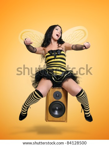 Young girl in costume bee unreal fly on speaker yellow background, stylized driving motorcycle concept - stock photo