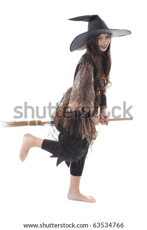 young girl in costume Halloween witch in black dress and hat fly on broom - stock photo