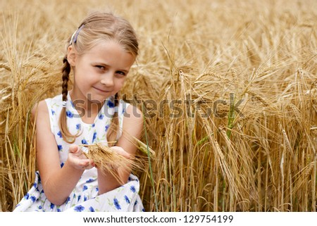 Young girl in country at cornfield. Focus on hands. - stock photo