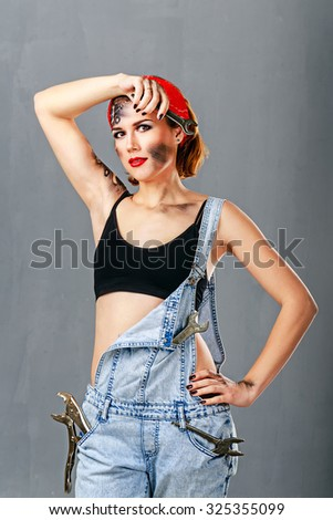 Young girl in denim overalls mechanic holding a wrench and wipes the sweat from her forehead. Professional work. Face art. Jack of all trades. The concept of severe girl. Pin-up girl style. - stock photo