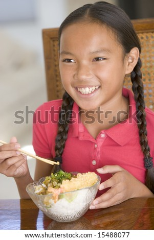 Young girl in dining room eating Chinese food smiling - stock photo