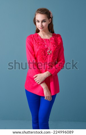 young girl in fashion red dress posing blue background