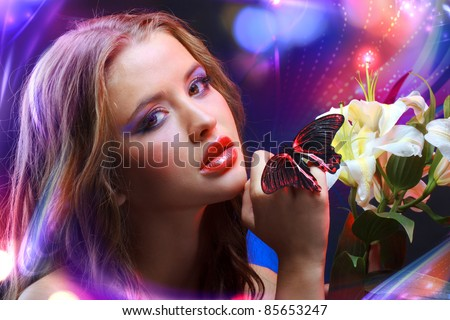 Young girl in front of shining abstract colourful floral background and tropical butterfly sitting on her finger - stock photo