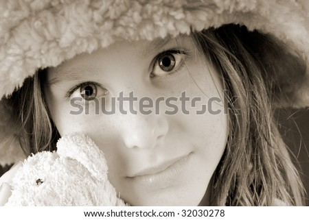 Young girl in furry hat holding favorite bear
