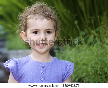Young girl in garden. Pretty child, toddler, wearing lilac purple top. She has blonde curly hair and deep brown eyes. She is looking at camera with a happy expression. The background is green garden. - stock photo