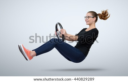 Young girl in glasses driver car with a wheel - stock photo