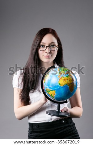 Young girl in glasses in a white blouse holding world globe over gray background and looking at camera