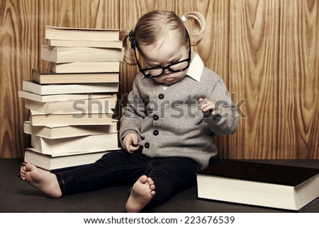 Young girl in glasses sitting by pile of books - stock photo