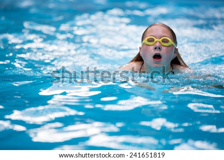 Young girl in goggles and cap swimming breast stroke style in the blue water pool - stock photo