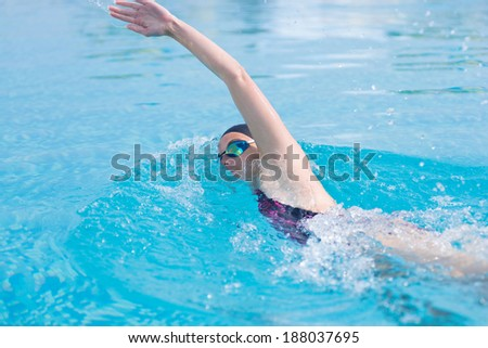 Young girl in goggles and cap swimming front crawl stroke style in the blue water pool - stock photo