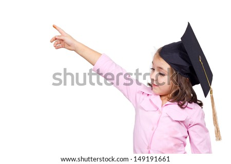 Young girl in graduation cap and gown pointing out of frame  - stock photo