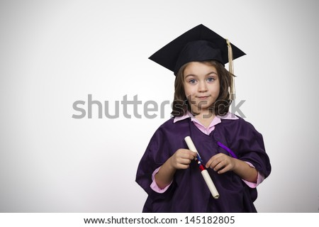 Young girl in graduation dress and gown with diploma over white background - stock photo