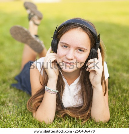 Young girl in headphones enjoys the music lying on the green grass. - stock photo
