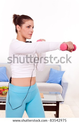 young girl in her apartment doing exercise with dumbbells