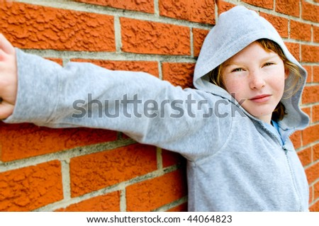 Young girl in hoodie against brick wall - stock photo