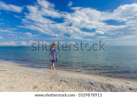Young girl in in blue dress walking at lake beach