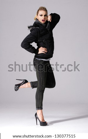 young girl in jacket standing posing on gray background