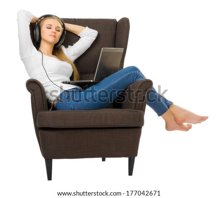 Young girl in jeans listen music on chair isolated - stock photo