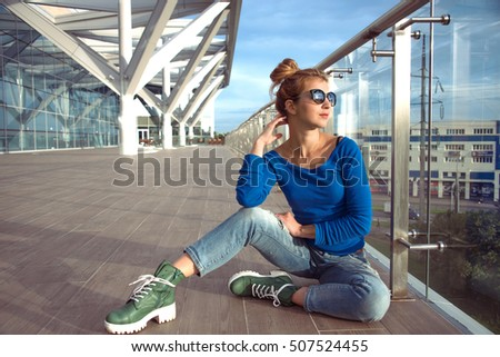 Young girl in jeans sitting on the outdoor glass veranda