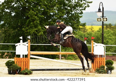 Young girl in jumping show - stock photo