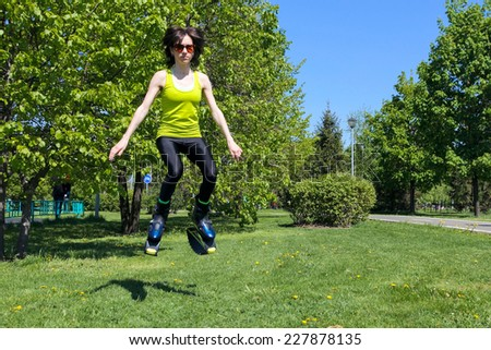 young girl in kengoo jumping boots doing fitness outdoors - stock photo