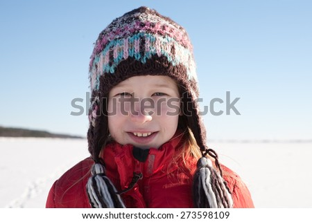 young girl in knitted cap on white snow field and blue sky background - stock photo