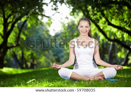 Young girl in lotus pose in the park