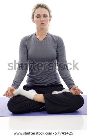 Young girl in lotus pose - meditation, isolated over a white background - stock photo