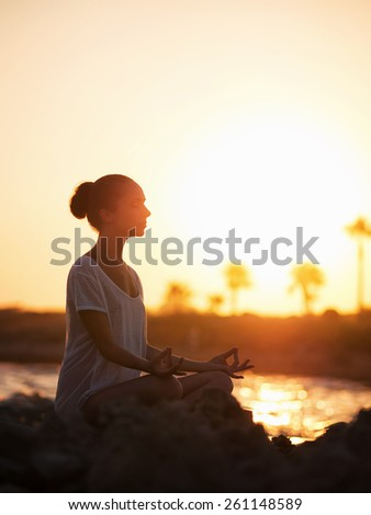 Young girl in lotus pose outdoors - stock photo