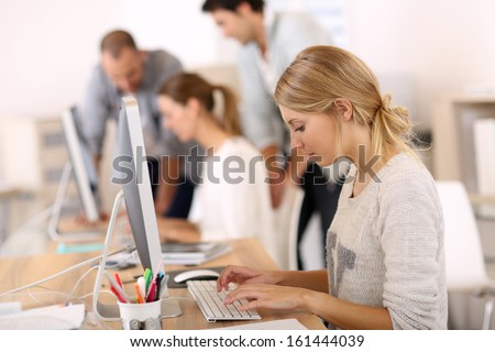 Young girl in office working on desktop computer - stock photo